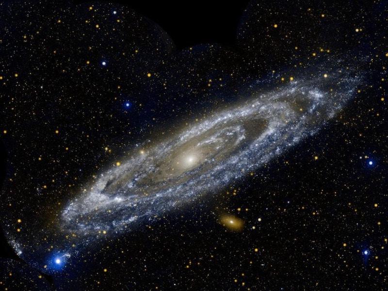 صورة لمجرة المرأة المسلسلة بين مئات المجرات الأخرى في الخلفية